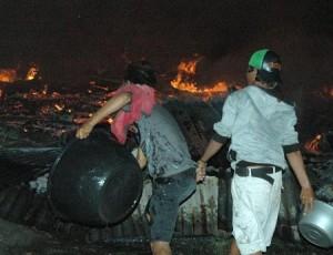 Warga menyiramkan air pada kobaran api yang membakar rumahnya dengan menggunakan ember